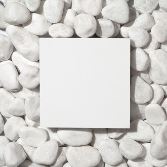 Weißes quadratisches podium auf weißem kieselsteinhintergrund. flache lage, draufsicht.