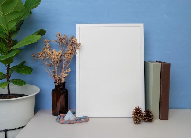 Weißes rahmenmodell für design oder text, bücher, getrocknete blumen im glas, tannenzapfen und antiker stein, der auf einem blauen wandhintergrund des holztischs sitzt