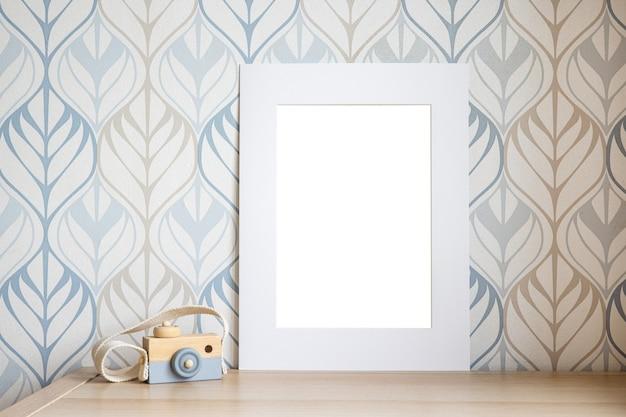 Weißes rahmenmodell für foto, druckkunst, text oder beschriftung, mit kinderzimmerdekorationen und spielzeug. leerer rahmen auf der seitenansicht des holztisches