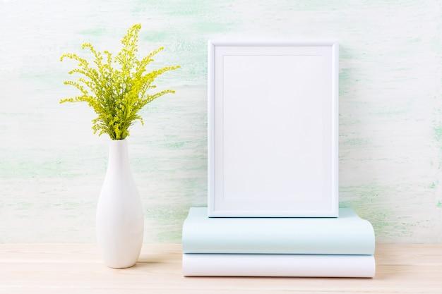 Weißes rahmenmodell mit dekorativem grünem gras und büchern