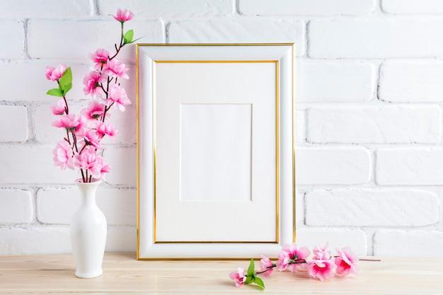 Weißes rahmenmodell mit rosa frühlingsblumenbündel
