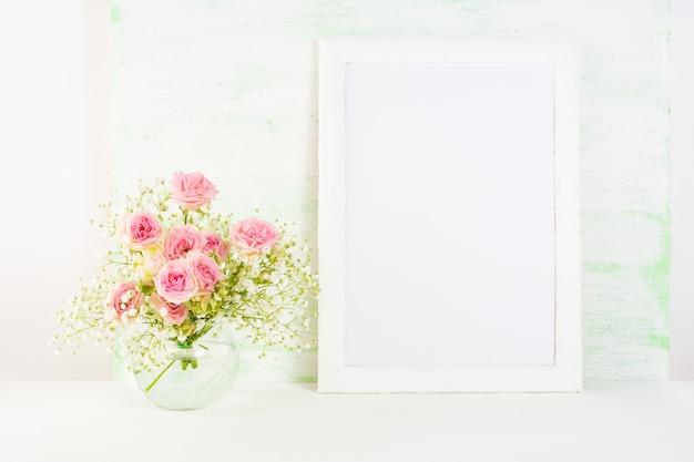 Weißes rahmenmodell mit rosarosenblumen