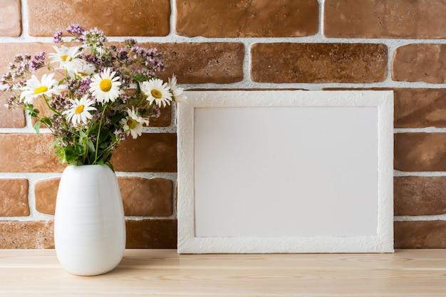 Weißes rahmenmodell mit wildblumenblumenstrauß in angeredeter vase