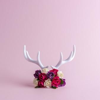 Weißes rentiergeweih mit rosenblüten
