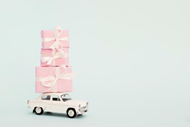 Weißes retro-spielzeugauto mit rosa geschenken