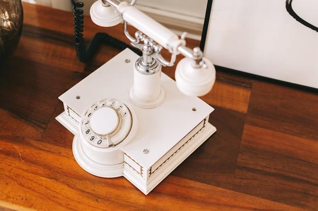 Weißes retro-telefon auf einem holztisch. nahansicht.