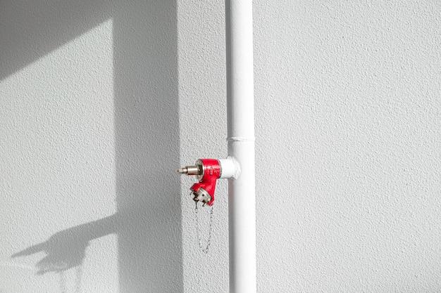 Weißes rohr mit rotem feuerlöscher