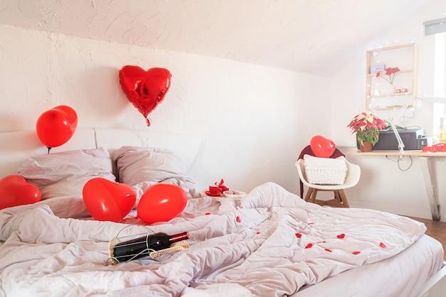 Weißes romantisches valentinstagschlafzimmer mit roten herzballons