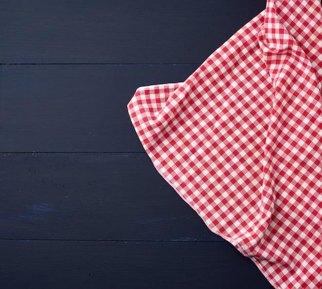 Weißes rotes kariertes geschirrtuch auf blauem hölzernem