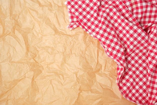 Weißes rotes kariertes geschirrtuch auf braunem papier