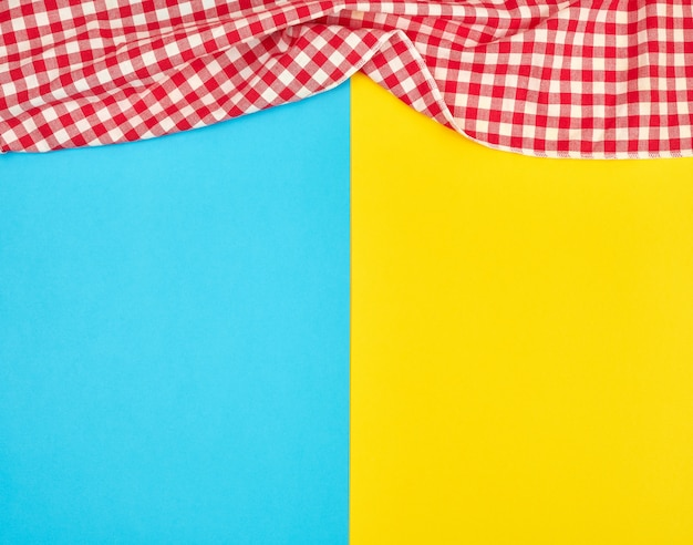 Weißes rotes kariertes geschirrtuch auf einem blauen gelben hintergrund