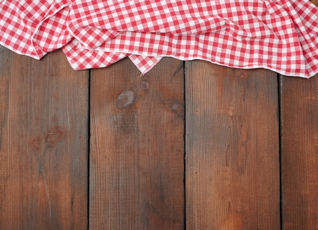 Weißes rotes kariertes geschirrtuch auf einem braunen holztisch
