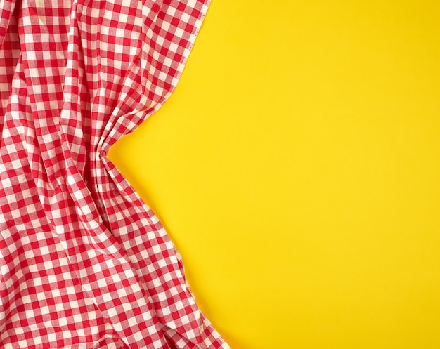 Weißes rotes kariertes geschirrtuch auf einem gelben hintergrund