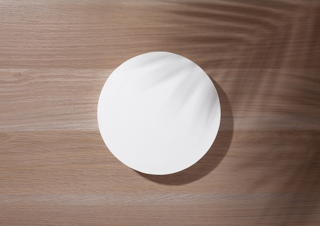 Weißes rundes podium auf holzhintergrund mit palmblattschatten. flache lage, draufsicht.