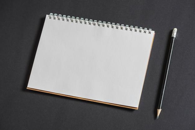 Weißes sammelalbum und bleistift auf grauem hintergrund