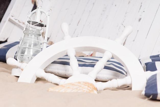 Weißes schiffsrad im sand begraben mit einer hurrikanlampe und leinwand vor dem umgedrehten deck eines holzbootes in einer darstellung eines schiffswracks, stillleben von modellen oder spielzeug