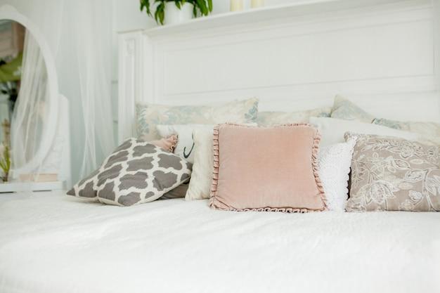 Weißes schlafzimmer im skandinavischen stil. auf dem bett liegen vier kissen. modernes interieur