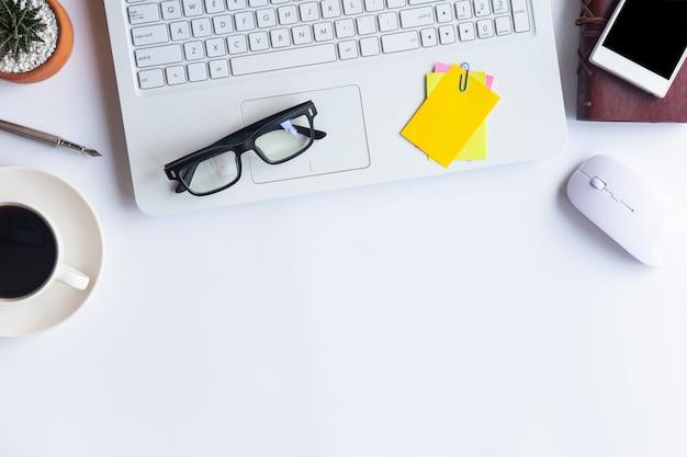 Weißes schreibtischbüro der draufsicht. arbeitsbereich auf tisch wesentliche elemente auf ebener fläche.