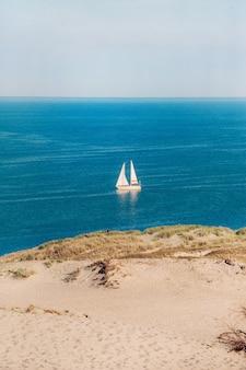 Weißes segelboot auf dem hintergrund der dünen und des blauen himmels im meer. weißes segelboot in der ostsee. lithuania.nida.