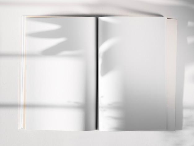 Weißes skizzenbuch auf einem weißen hintergrund mit einem blattschatten