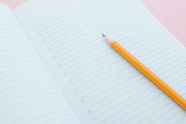 Weißes skizzenbuch mit orange bleistift. notizbuch und bleistift