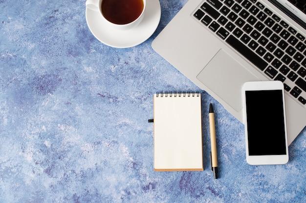 Weißes smartphone mit schwarzem leerem bildschirm auf schreibtisch mit laptop, leerem notizbuch und tasse tee. mock-up des telefons.