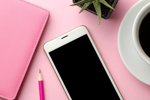 Weißes smartphone und eine tasse kaffee und ein rosa notizblock auf einem leuchtend rosa hintergrund. sicht von oben