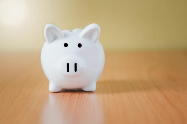 Weißes sparschwein für einsparungen mit geld und planungsschritt bis zum wachstum, geld sparen für pensionsfonds und das zukunftsplan-konzept.