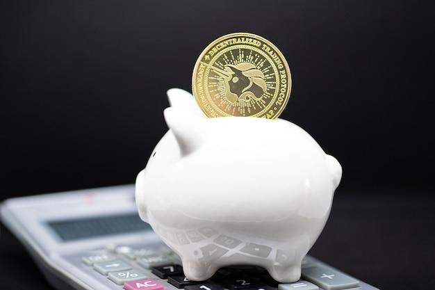 Weißes sparschwein und gole-bitcoin stehen auf dem taschenrechner und schwarzem hintergrund. es zum sparen von geldkonzept und zum halten der kryptowährung.