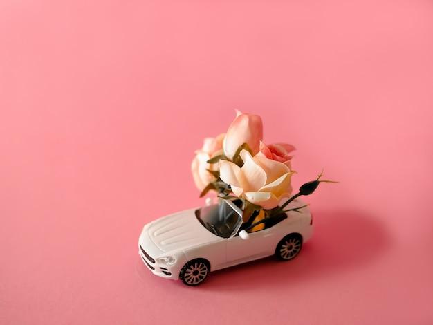 Weißes spielzeugauto, das rosafarbenen blumenstrauß auf rosa hintergrund liefert
