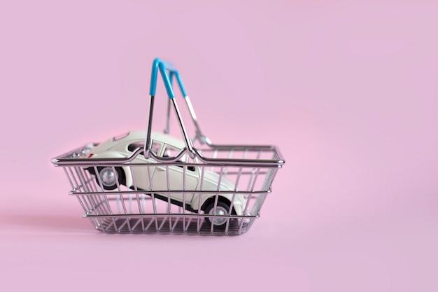 Weißes spielzeugauto im mini-einkaufskorb auf rosa hintergrund. autokaufkonzept