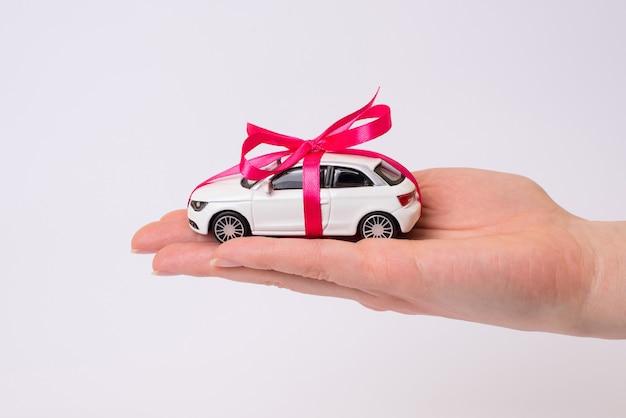 Weißes spielzeugauto mit rosa bogen auf hand lokalisiert