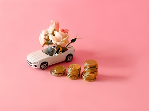 Weißes spielzeugauto nah an den münzen, die blumenstrauß von blumen auf rosa hintergrund liefern.