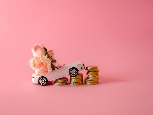 Weißes spielzeugauto nah an den münzen, die rosafarbenen blumenstrauß auf rosa hintergrund liefern