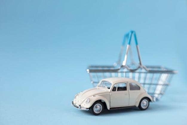 Weißes spielzeugauto neben einkaufskorb auf blauem hintergrund. autokaufkonzept