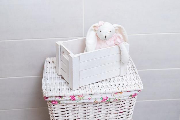 Weißes spielzeugkaninchen in einem rosa kleid sitzt in einer weißen holzkiste auf einem weidenwäschekorb