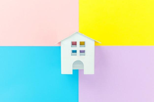 Weißes spielzeugminiaturhaus lokalisiert auf blauem gelbem rosa purpurrotem buntem modischem geometrischem pastellhintergrund