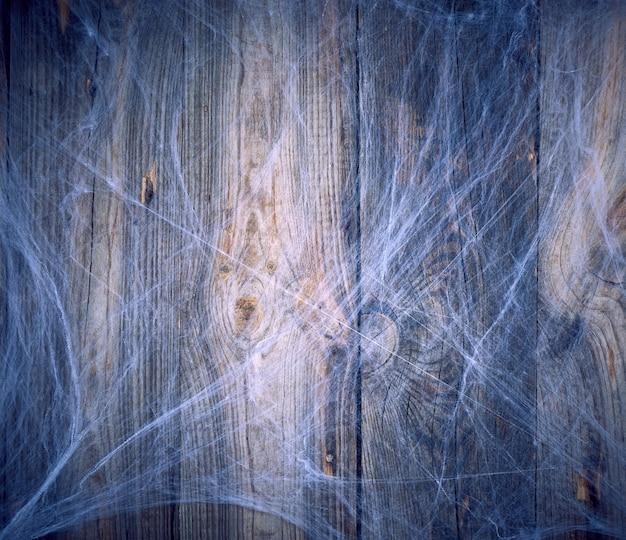 Weißes spinnennetz in der ecke der zusammensetzung, grauer hölzerner hintergrund von den alten brettern