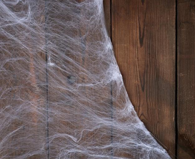 Weißes spinnennetz in der ecke des holztischs