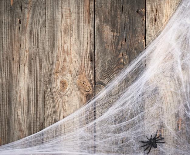 Weißes spinnennetz mit schwarzen spinnen auf einer grauen holzoberfläche vom hintergrund der alten bretter