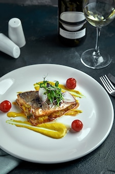 Weißes steak von gegrilltem fisch auf gemüsekissen und gelber soße, mit tomaten und frischen kräutern. fischen sie auf weißer platte mit weißwein auf dunklem schönem hintergrund. nahansicht. platz