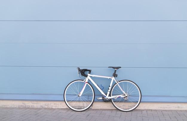 Weißes straßenrad auf einem pastellblauen hintergrund