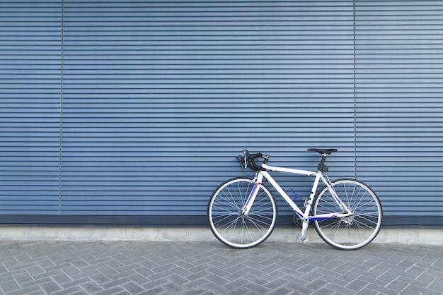Weißes straßenrad steht auf dem hintergrund einer blauen wand