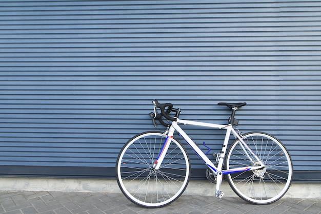 Weißes straßenrad steht auf dem hintergrund einer grauen wand