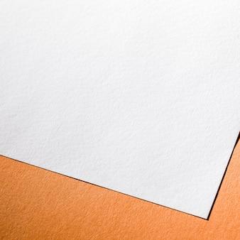 Weißes strukturiertes papier auf orangefarbenem hintergrund