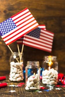 Weißes süßigkeitsglas mit brennenden kerzen und usa-flagge auf hölzernem schreibtisch