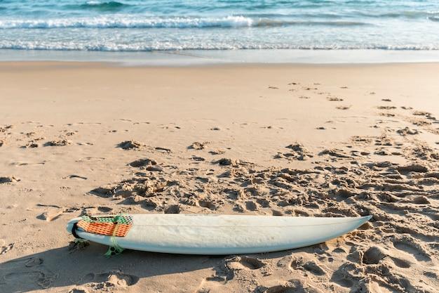Weißes surfbrett, das auf sand liegt