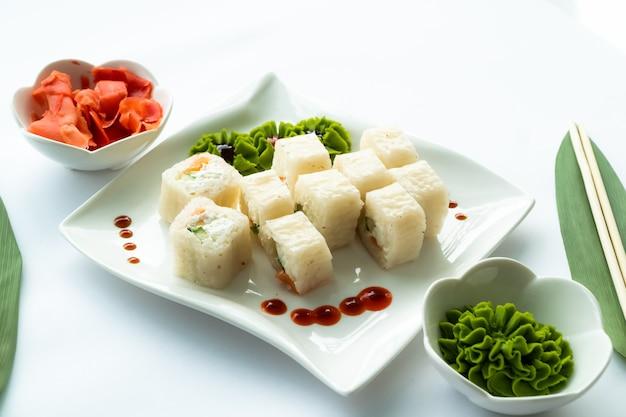 Weißes sushi auf weißem teller und weißer oberfläche mit wasabi, ingwer und essstäbchen