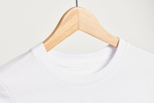 Weißes t-shirt auf einem hölzernen kleiderbügel