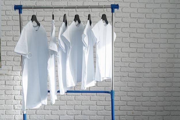Weißes t-shirt, das auf kleiderbügel gegen backsteinmauer hängt, kopieren raum